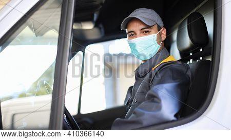 Smiling deliverer man driving a van, covid coronavirus concept