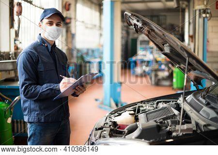 Masked car mechanic repairing a car, covid coronavirus work concept
