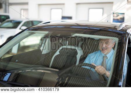 Business man sitting on a car at a car dealer saloon