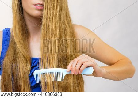 Young Woman Combing Long Healthy Blonde Hair, Using Comb
