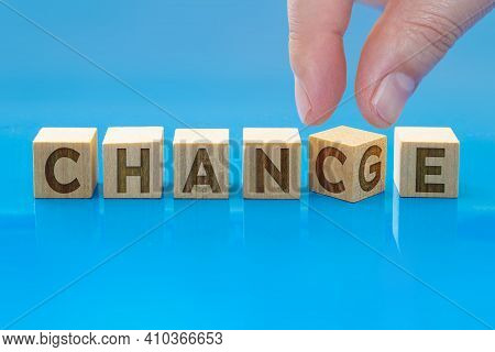 A Person With Wooden Cubes With Word `change` To `chance` On Blue Background. Concept: Personal Deve