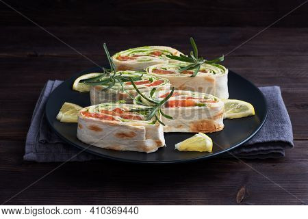Rolls Of Thin Pita Bread And Red Salted Salmon With Lettuce Leaves On A Black Ceramic Plate, Dark Wo