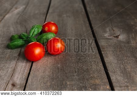 Red Cherry Tomatoes With Green Basil On The Gray Wooden Background
