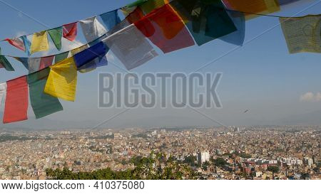 Waving Prayer Flags Against Cityscape. View Of Waving Multicolored Prayer Flags On Strings Above Cit