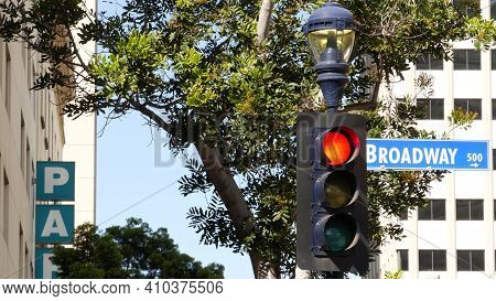 Broadway Street Name, Odonym Sign And Traffic Light On Pillar In Usa. Road Intersection In Downtown
