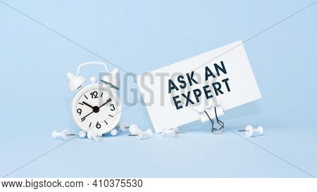 Ask An Expert - Concept Of Text On Business Card. Closeup Of A Personal Agenda On Blue Background