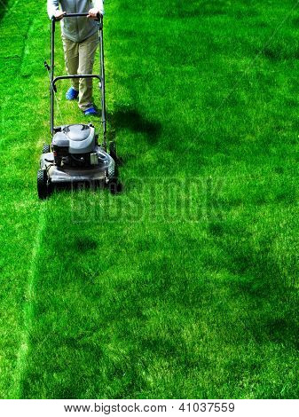 Young Girl Mowing green grass lawn with push mower