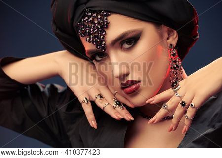 Arabian beauty, fashion. Close up portrait of a beautiful oriental woman with traditional make-up, black turban and jewelry on a black background. Make-up and cosmetics.