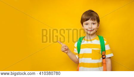 Happy Little School Boy Pointing Finger At Yellow Background Copy Space. Back To School. Attention C