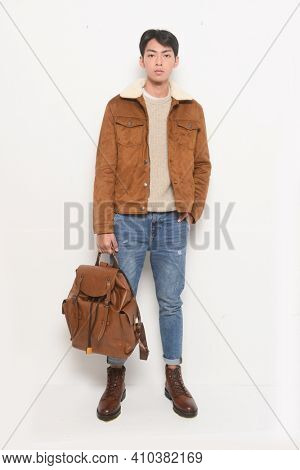 Full body handsome young man in brown jacket with sweater with jeans ,leather boots,holding backpack  posing with on white background
