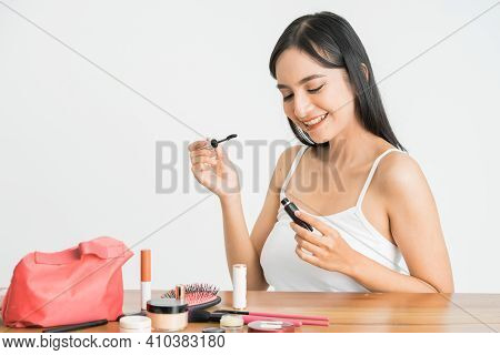 Mixed Race Asian Woman Putting Mascara On Eyelashes On White Background