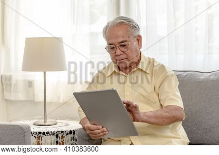 Asian Senior Man Using Tablet And Looking For Insurance After Retirement. Grandfather Stay Alone At