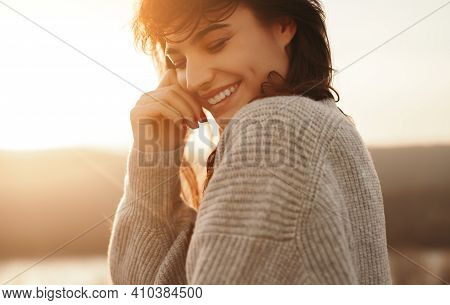 Side View Of Charming Shy Female Cheerfully Smiling On Background Of Sundown Sky In Nature