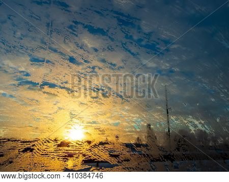 Car Window Glass Covered With Ice And Frost In Winter With Beautiful Yellow Sunrise