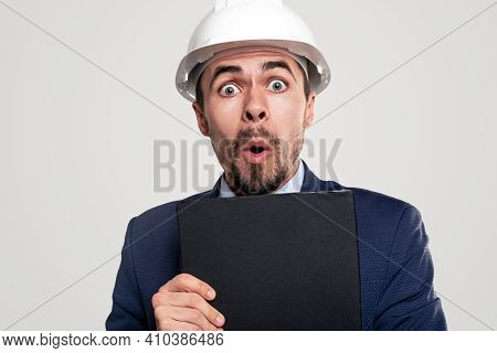 Funny Surprised Male Construction Employee In Formal Suit And Hardhat Holding Clipboard And Looking