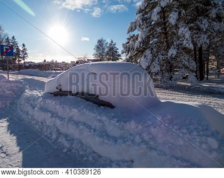 Car Covered With With A Lot Of Snow After Heavy Snow Storm. Accumulation Of Snow On Surfaces In Wint