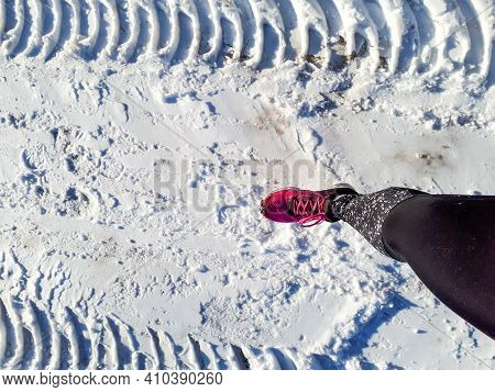 View From Above On Woman Running In Running Tights And Shoes In Snow. Athlete Woman Runner In Winter