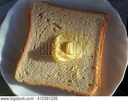 Slice Of Toast Bread With A Piece Of Butter On A White Plate In A Sunlight
