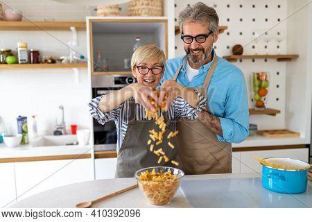 Senior Couple Having Fun, Cooking In Home Kitchen