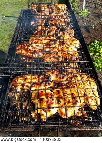 Grilling Chicken Meat On The Barbecue Charcoal Grill In The Garden On Sunny Day