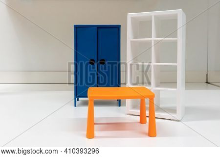 Miniature Toy Orange Plastic Table, White Shelf And Blue Cabinet On White Room  Background.