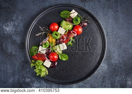 Fresh Greek Salad With Tomato, Cucumber, Bel Pepper , Olives And Feta Cheese On Black Plate, Top Vie