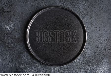 Empty Round Black Plate On Dark Moody Dark Background With Copy Space. Overhead View