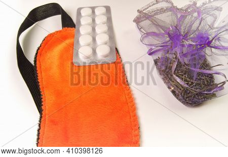 A Composition With Dried Lavender Flowers, An Orange Sleep Mask And Sleeping Pills On A White Backgr