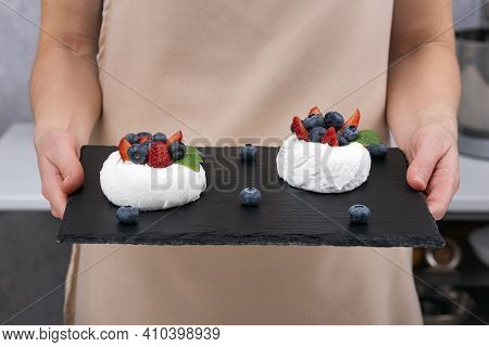 Cake Anna Pavlova On Black Tray In The Woman's Hands. Meringue Cake With Fresh Berries.