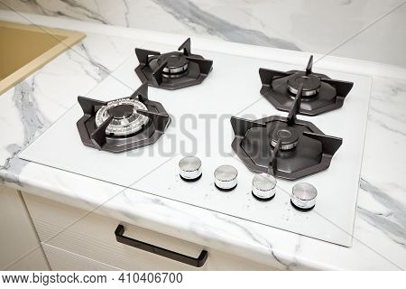Modern Gas Stove On Counter Top White Closeup. Hob Gas Stove Using Natural Gas Or Propane For Cookin