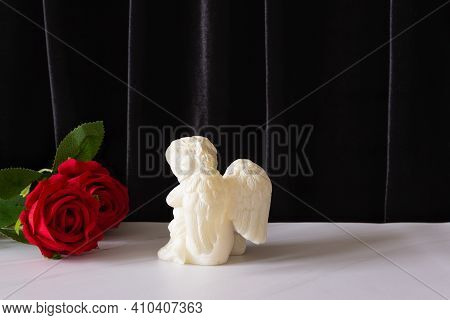 A Candle In The Form Of An Angel With Wings And A Red Rose. The Funeral Symbol, The Concept Of Condo