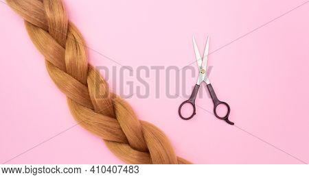 A Braid Of Light Brown Artificial Hair On A Pink Background And Scissors. The Concept Of A Hair Salo