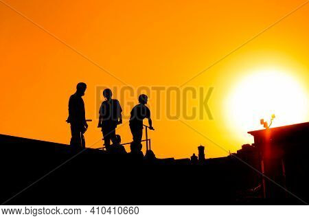 Unrecognizable Group Of Teenage Boy Silhouettes With Scooters Standing Together Against Orange Sunse