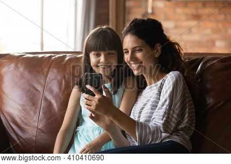 Smiling Latino Mom And Little Daughter Use Smartphone