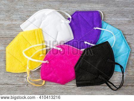 Colorful FFP2 masks on a wooden background
