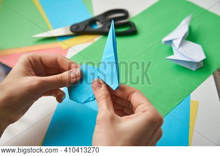 Origami Lessons. Woman Make Origami Easter Rabbit From Color Paper. Diy Concept
