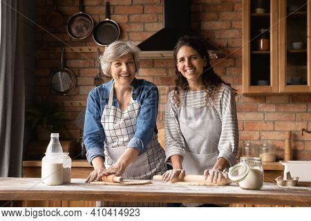 Portrait Of Smiling Latino Mom And Daughter Baking Together