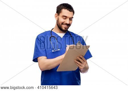 healthcare, profession and medicine concept - happy smiling doctor or male nurse in blue uniform writing medical report on clipboard over white background
