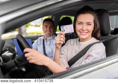 driver courses, exam and people concept - young woman with license and driving school instructor with clipboard in car