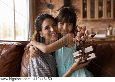 Portrait Of Happy Latino Mom And Daughter Hugging