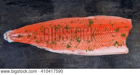 Chilled Salmon Fillet On The Skin Sprinkled With Chopped Dill Lies Skin Side Down On A Dark Surface