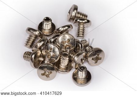 Small Pile Of Machine Screws With Cross Recessed Pan Head And White Anti Corrosion Coating On A Whit
