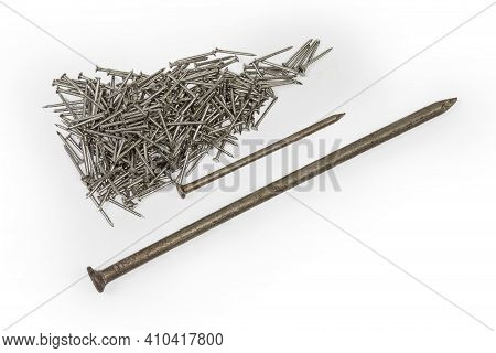 One Big And One Medium Size Common Construction Nails And Pile Of Small Nails With White Anti Corros