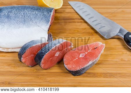 Uncooked Salmon Steaks And Not Sliced Piece Of Fish, Kitchen Knife On A Bamboo Cutting Board, Close-