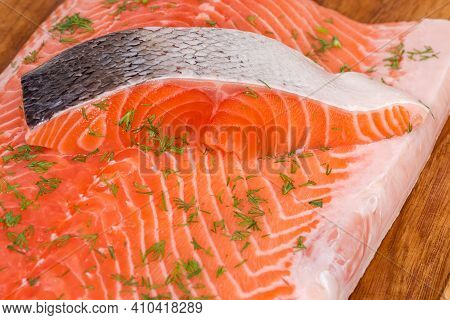 Slice Of Raw Chilled Uncooked Salmon On Skin Lies On Salmon Fillet Sprinkled With Chopped Dill On A