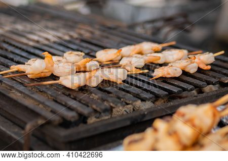 Process Of Cooking Shrimp, Prawn Skewers On Black Grill Grate At Summer Outdoor Food Market, Close U