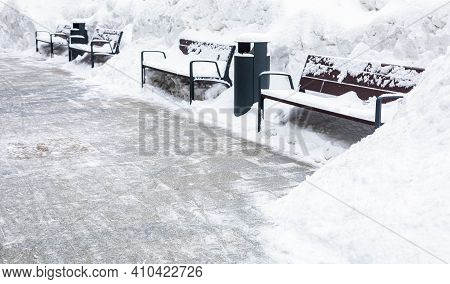 Three Benches Covered With Snow. In Front Of Them Cleared From Snowdrifts Asphalt. Place For The Ins