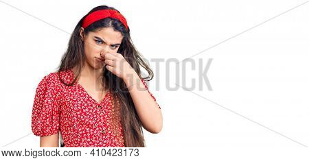Brunette teenager girl wearing summer dress smelling something stinky and disgusting, intolerable smell, holding breath with fingers on nose. bad smell