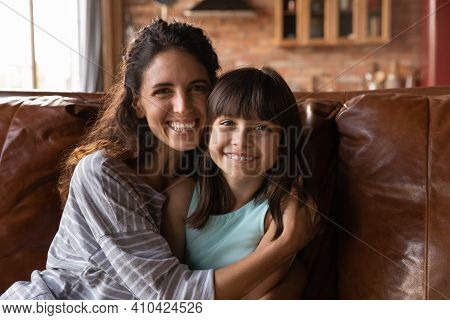 Portrait Of Smiling Latino Mom Cuddle With Daughter