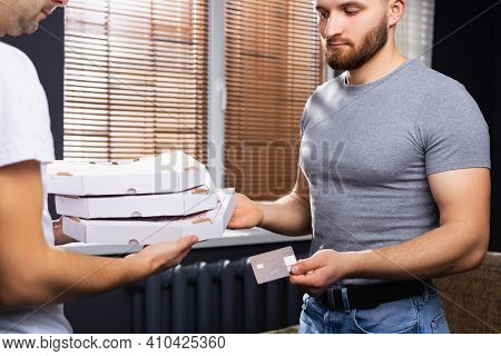 Young Businessman Using Bank Terminal And Card To Pay For Food Delivery At Workplace, Closeup, Cropp